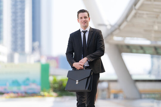 Successful businessman going on business meeting holding briefcase