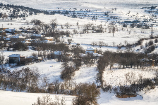 Wonderful winter landscape with a small village nestled between snow-covered hills