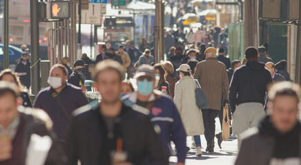 Crowd of people walking street wearing masks in New York City during Covid 19 coronavirus pandemic...