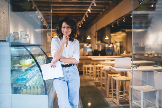 Half length of cheerful Caucaisan entrepreneur feeling success in franchise coffee shop standing in doorway and smiling at camera, happy self employed woman working in local cafeteria industry