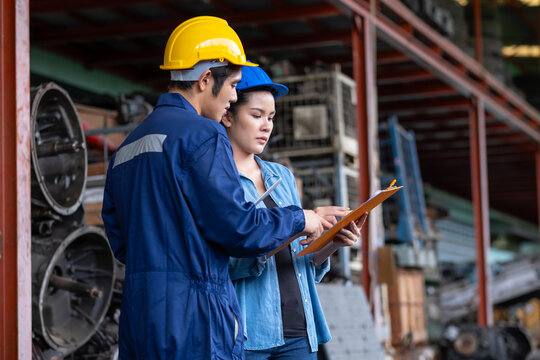 Confident Asia engineer woman worker wears a safety helmet holding clipboard and discusses with a man in the automotive spare parts warehouse. stock management concept. Many old engines parts