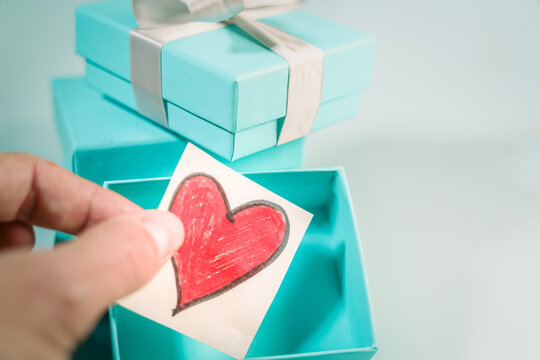 Hand putting a drawn heart inside a turquoise gift box. Suitable for concepts like luxury gift, anniversary, Valentine's day, Mother's day or christmas