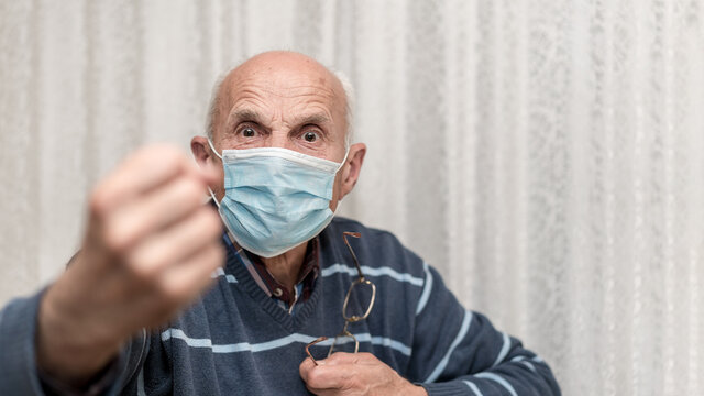 angry aggressive elderly man wearing face mask showing big fist self isolation and coronavirus concept