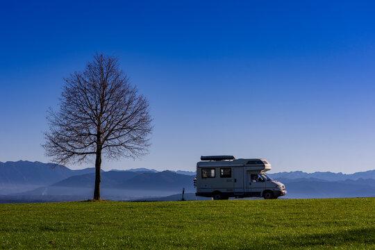 Urlaub in Oberbayern: Blaues Land mit Bergen im Hintergrund in der Nähe von Peißenberg - Camper auf dem Weg zum Gipfel Parkplatz