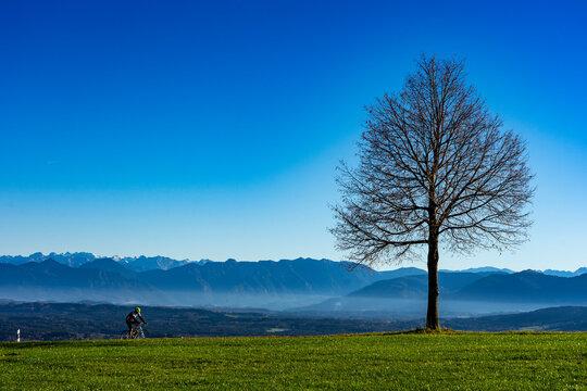 Urlaub in Oberbayern: Blaues Land mit Bergen im Hintergrund in der Nähe von Peißenberg - Rennradfahrer in der nachmittags Herbststimmung bei der Abfahrt vom Gipfel