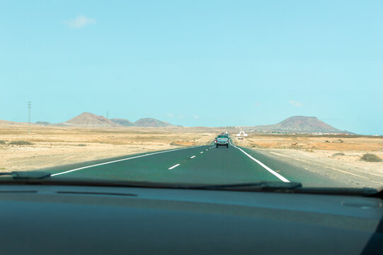 Desert road in arid and mountainous landscape during a hot summer day.