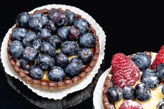 Tartelette mit Blaubeeren, Himbeeren und Erdbeeren vor einem schwarzem Hintergrund