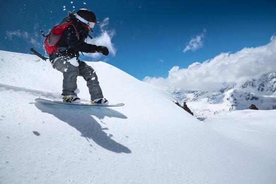 Woman snowboarder has fun riding on snowy off-road freeride in the Italian Alps. Professional sportswoman snowboard freeride