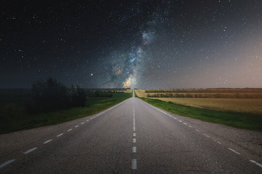 Country asphalt road in summer at night with starry sky and milky way. Road to dreams