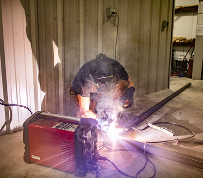 A man welds two pieces of metal together with an arc welder in a shop.