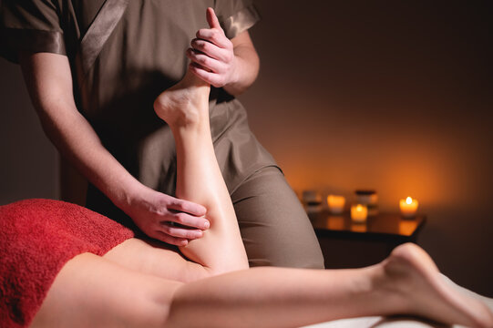 Professional massage of female feet by a man masseur in a dark spa salon with candles