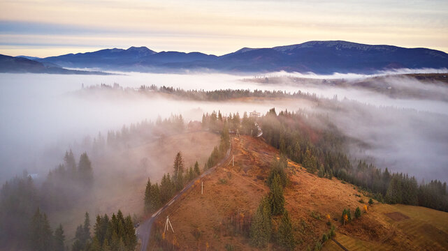 Cold November morning. Morning fog in mountain valley. Forest covered by low clouds. Misty fall woodland