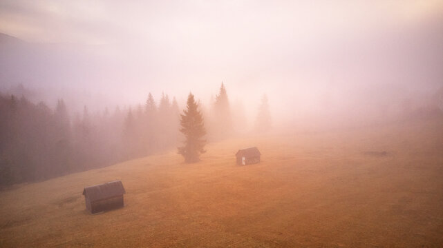 Morning fog in mountain valley. Forest covered by low clouds. Alpine village. Autumn rural landscape.