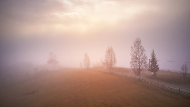 Morning fog in mountain valley. Forest covered by low clouds. Alpine village. Autumn rural landscape. Cold November morning.