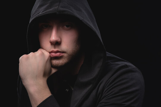 Portrait of a large attractive man in a black hood holds his chin with his hand in a pensive pose. Secretive face in the shadow of the outlaw