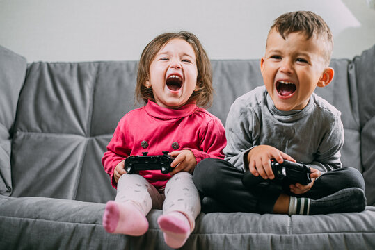 Brother and sister with a gamepad in their hands playing games shouting having fun