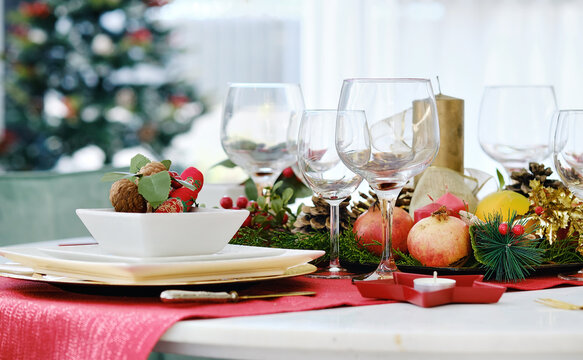 Christmas dinner and New Year celebration concept. Close up decoration on the table ready for quest reception, ornate table setting with candle and xmas wreath
