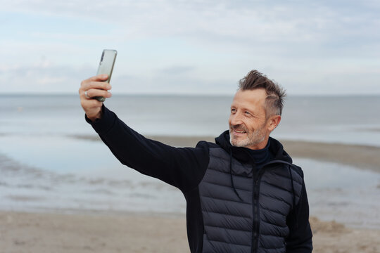 Fit active man taking a selfie at the beach