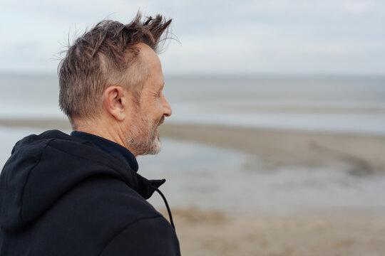 Man taking a walk on a windy cold beach