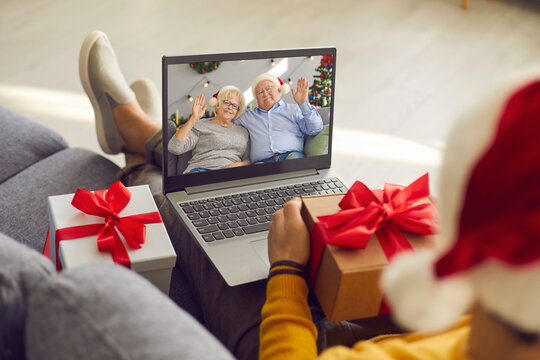 Grown-up son holding present and video calling his senior parents on Christmas Day