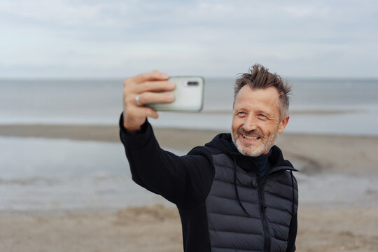 Smiling man posing for a selfie on his mobile