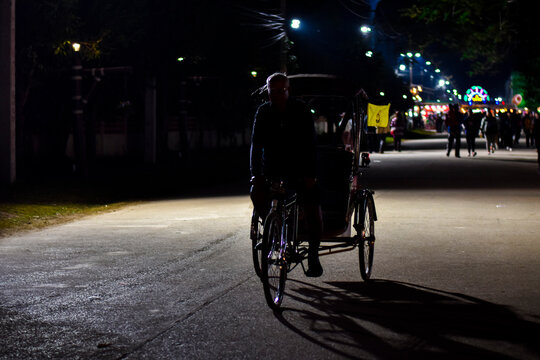 Full Length Of Man Cycling Bicycle Cart On Road At Night