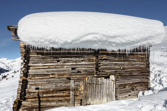Skihütte mit Schnee am Schindeldach mit Eiszapfen