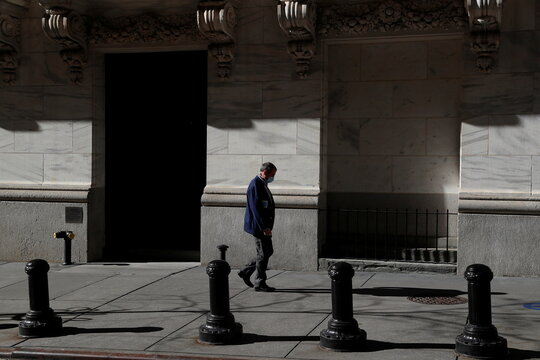 A trader wearing a protective face mask walks, as the global outbreak of the coronavirus disease (COVID-19) continues, at the New York Stock Exchange (NYSE) in the financial district of New York