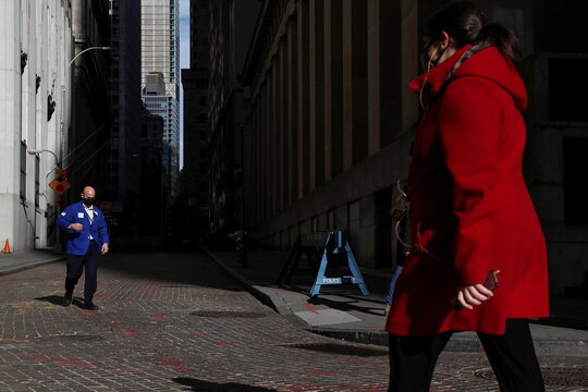 A trader wearing a protective face mask walks, as the global outbreak of the coronavirus disease (COVID-19) continues, outside the New York Stock Exchange (NYSE)  in the financial district of New York