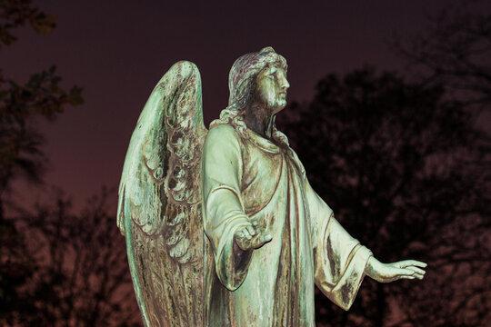 Jesusfigur angeblitzt gegen einen dunklen Abendhimmel