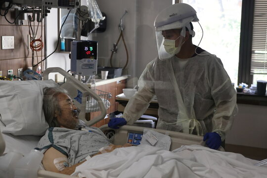 Registered nurse Vincent Encarnacion, 45, chats to patient Keith Endo, 68, in the COVID-19 intensive care unit, as the global outbreak of the coronavirus disease (COVID-19) continues, at Providence Saint Joseph Medical Center in Burbank