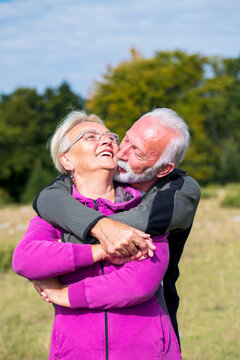 Elderly couple embracing in autumn park. Enjoying in love.
