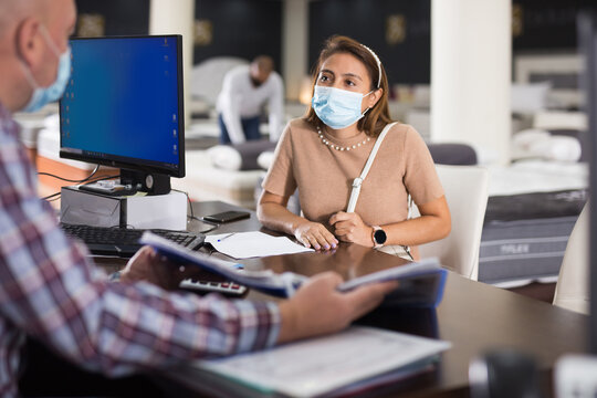 Hispanic woman in protective mask consulting with salesman when choosing new mattress in furniture store. Concept of social distancing in coronavirus pandemic