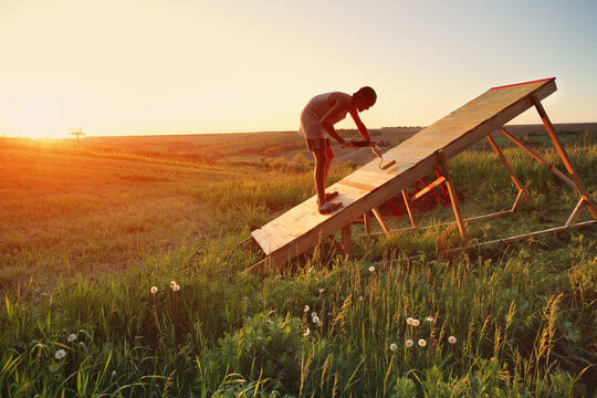 Young Caucasian man paints new mtb gap in the field at sunset. The springboard is designed for jumping on a bicycle and a motorcycle.