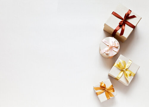 Four holiday gifts are wrapped in eco kraft paper and tied with satin ribbons. Gift boxes on light background. Festive delivery of goods. Surprises for family celebration. Flat lay, copy space, mockup