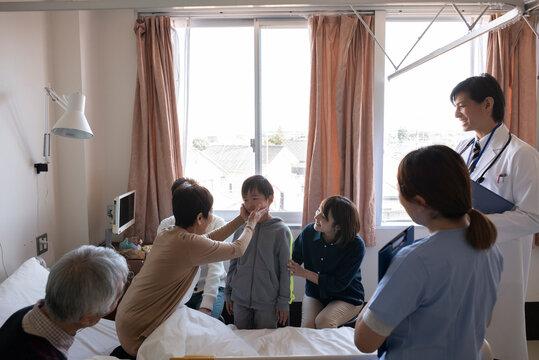 お見舞いに来た孫に触れる入院中のおばあちゃん