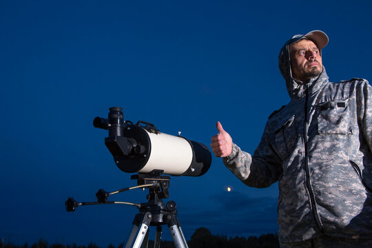 A male astronomer observes the sky through a telescope. Amateur astronomy concept.