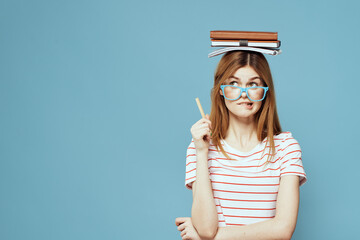 Female student with books on her head science education blue background emotions gesturing with...