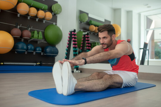 Bearded male bending forward, touching his toes, stretching hamstrings