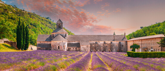 Notre-dame De Senanque Abbey, Vaucluse, France. Beautiful Landscape Lavender Field And An Ancient Monastery Abbaye Notre-dame De Senanque. Elevated View, Panorama. Altered Sunset Sky
