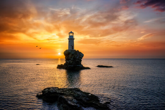 A lonely lighthouse named Tourlitis on a rock in the calm, sea of Greece during a cloudy summer sunrise, Andros island, Cyclades
