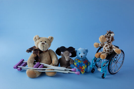 International day of persons with disabilities. Wheelchair with toys sign of different disabilities on blue background.