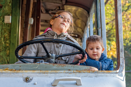 Childrens play in an abandoned bus. A girl drive a bus. The girl turns the steering wheel in the abandoned bus.