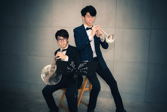Boy And Man Playing Musical Instruments Against Wall