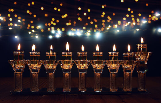 image of jewish holiday Hanukkah background with crystal menorah (traditional candelabra) and oil candles