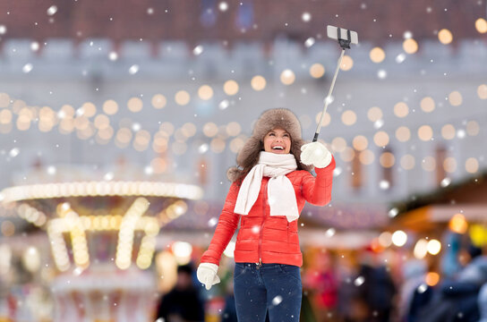 people, technology and winter holidays concept - happy woman taking picture with smartphone on selfie stick over christmas market on background
