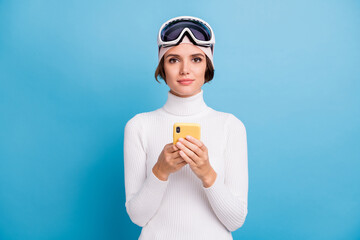 Photo of brown bob haired woman hold phone wear ski gear serious mood isolated on blue color background Wall mural