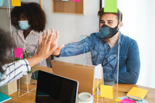 Young people working inside a coworking behind safety plexiglass during coronavirus outbreak - Social distance and startup concept - Focus on man face
