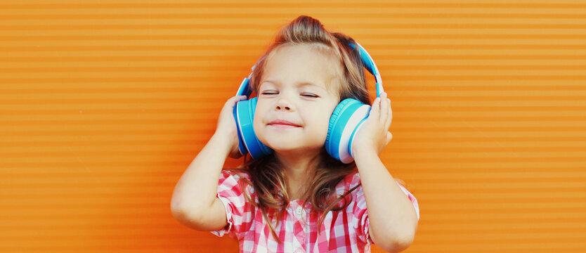 Portrait of little girl child in wireless headphones listening to music over orange background