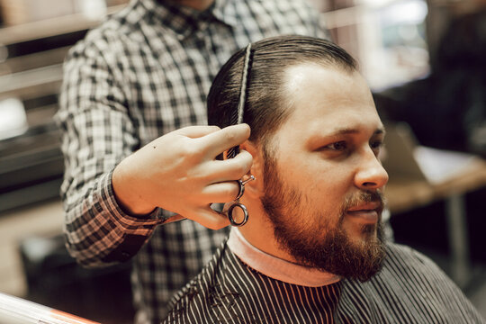 Close up haircut in the barbershop. Young bearded man getting haircut while sitting in chair at barbershop. Hairdresser cuts hair with scissors and a comb
